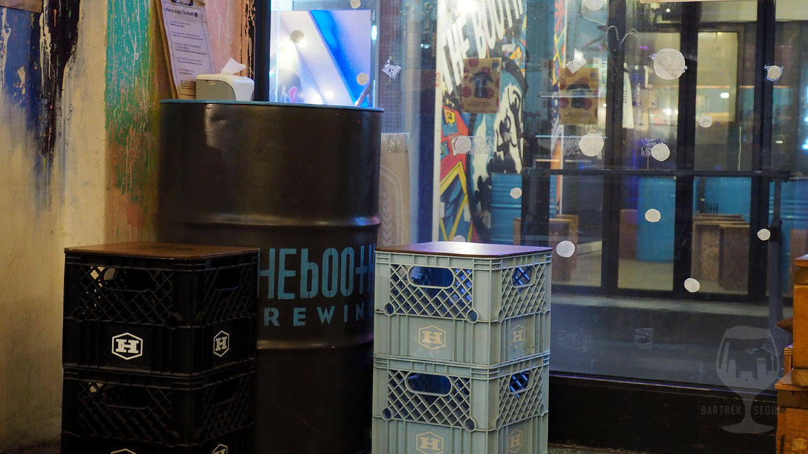 Black metal barrel as table with blue the booth print.