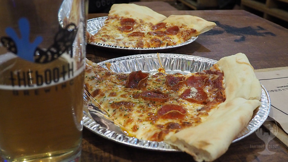 Two huge slices of pepperoni monster pizza at the booth craft beer pub.