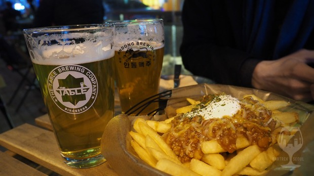 Two glasses of craft beer and a plate of french fries with sauce.