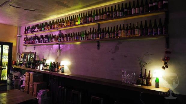 Two shelves full of empty sour beer bottles.