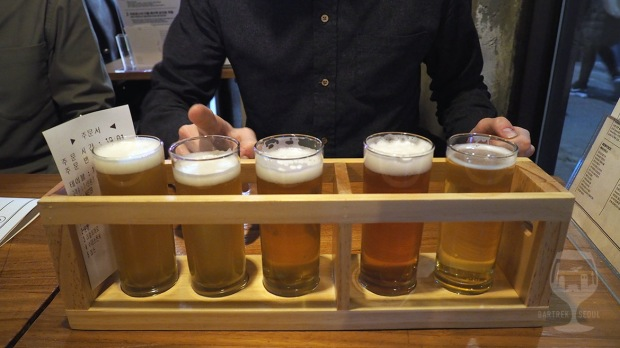 Five small glasses of craft beer on a wooden tray.