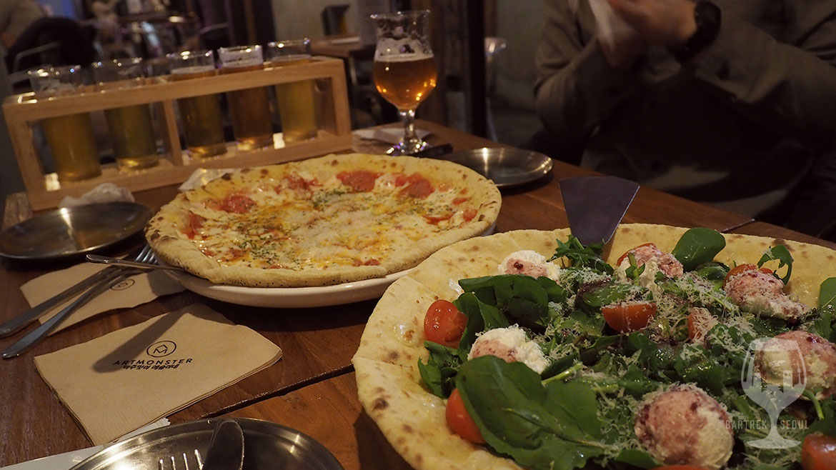 A picture of two pizzas and a glass of nice IPA craft beer.