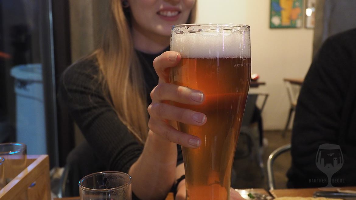 Picture of girl holding a huge glass of IPA craft beer.