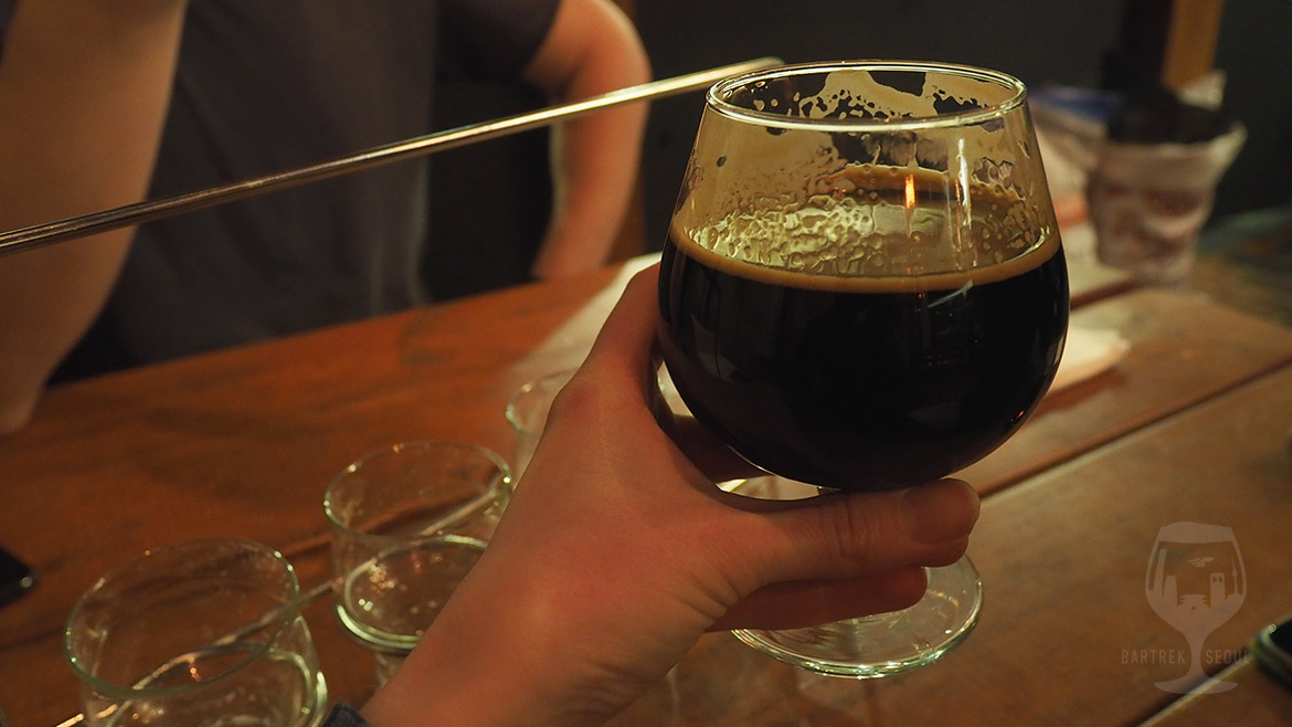 Picture of a hand holding round glass of mocha stout beer.