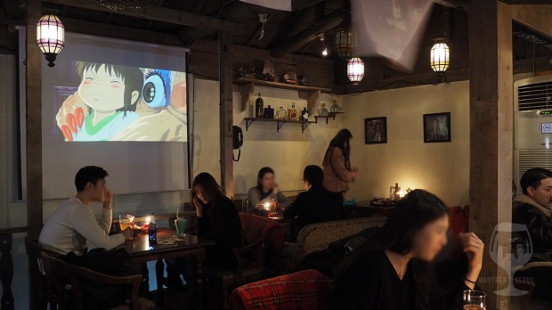 Anime cartoon playing on the screen. The pub full of people.