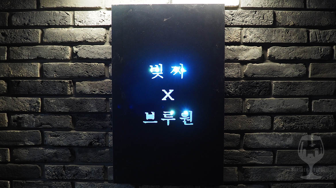 Metal sign in front of the entrance door, saying Beezza x Brewone in Korean.
