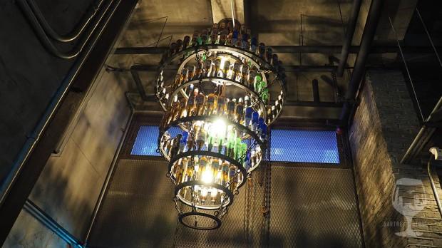 A huge chandelier made of metal rings and beet bottles.