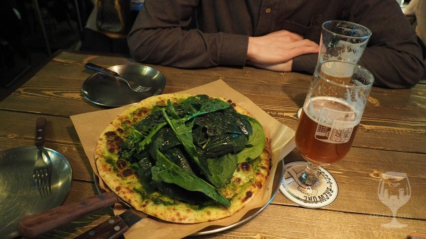 Two glasses of craft beer and a spinach filled pizza.