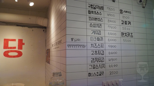 The food menu is also written with black market on the white tiles on the wall.