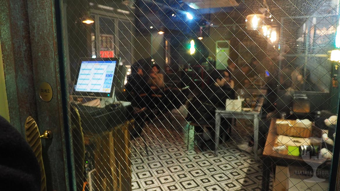 Photo taken through glass door. People sitting in the bar.