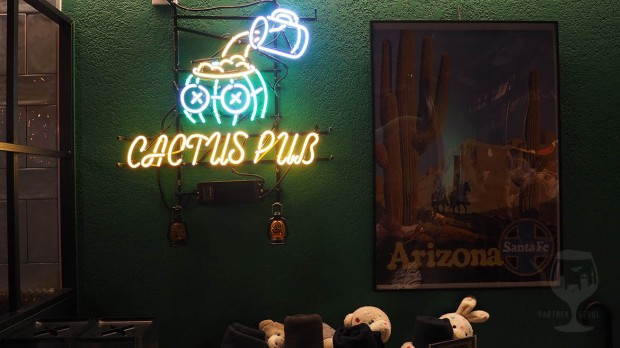 Cactus character neon sign. Pouring beer to the cactus guys brains.