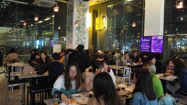Many people enjoying food and korean craft beer.