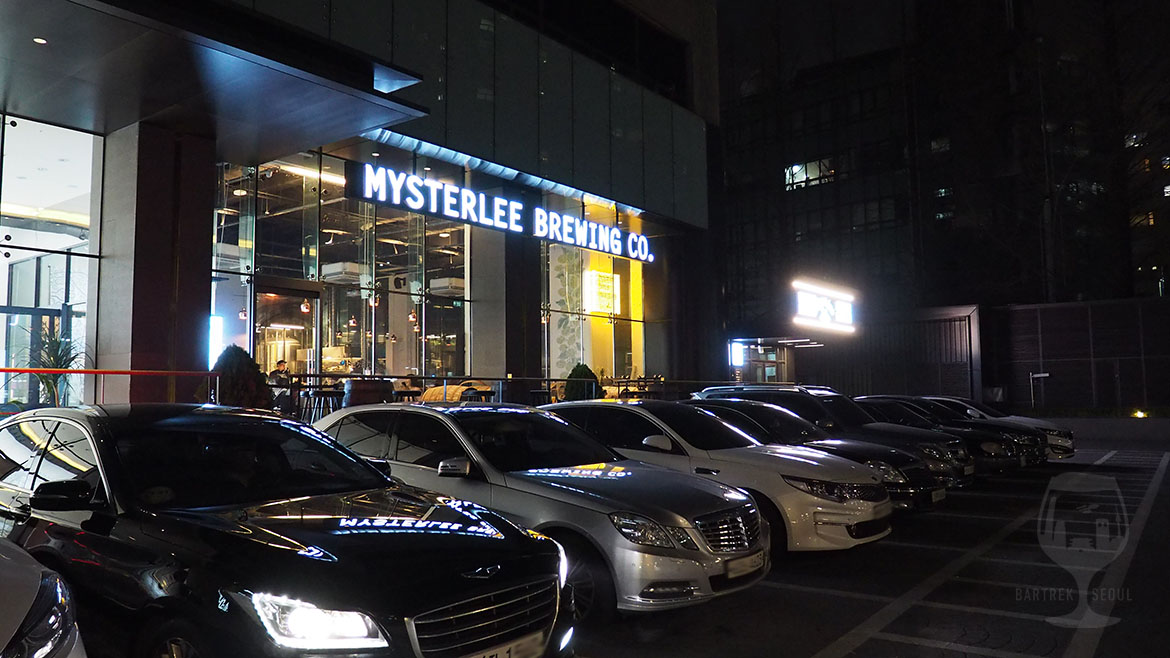 Mysterlee Brewing co. tap house from outside the building. Big glass windows and a light sign.
