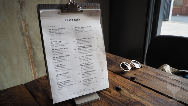 Picture of the craft beer menu stand. Wooden table.